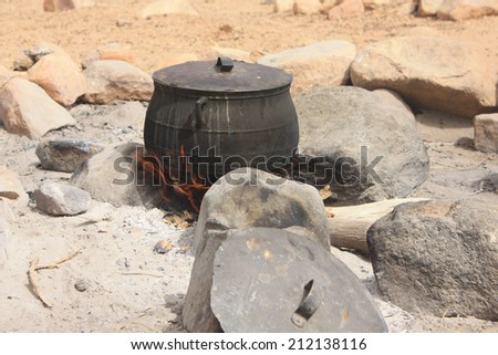 Old and blackened pot on the fire - stock photo