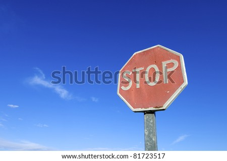 old and damaged stop sign against a blue sky
