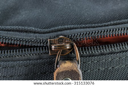 Old and damaged zipper on black cloth - stock photo