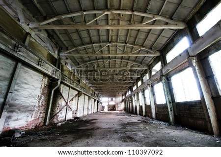 Old and deserted plant symmetrical interior with weathered walls and overlap - stock photo