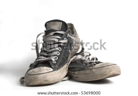 Old and dirty black canvas sneakers - stock photo