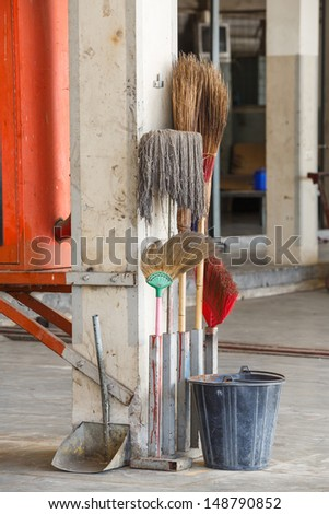 Old and dirty cleaning equipments in car garage, bucket, scoop, broom and mob - stock photo