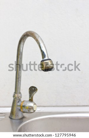 Old and dirty kitchen faucet and sink. - stock photo