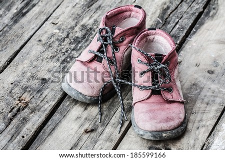 old and dirty little baby booties on wood floor - stock photo