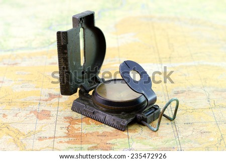 old and dirty military compass on the map - stock photo