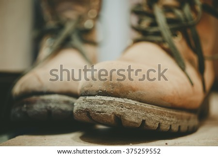 Old and dirty yellow boots in mud - stock photo