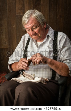 Old and gray pensioner smoking his pipe - stock photo