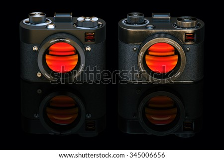 Old and new retro style digital camera isolated on black background. 3d render