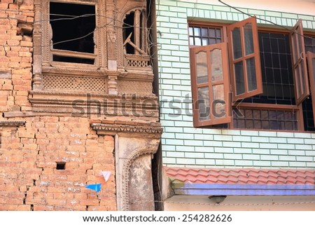 Old and new: traaditional red brick with carved wooden windows and modern wall tile facades-houses in the old city area. Dhulikhel-Kavrepalanchok distr.-Bagmati zone-Nepal. - stock photo