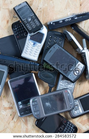 Old and obsolete cellphone on wooden background - stock photo