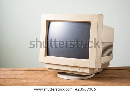 old and obsolete computer monitor on old wood table with concrete wall background - stock photo