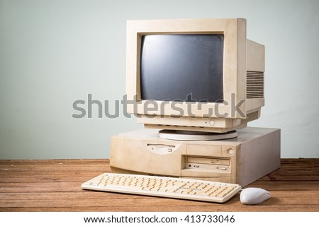 old and obsolete computer on old wood table with concrete wall background - stock photo