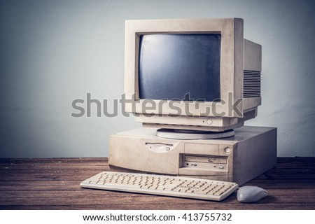 old and obsolete computer on old wood table with concrete wall background, vintage color tone