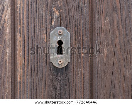Old and rusty door lock, keyhole in wooden door.