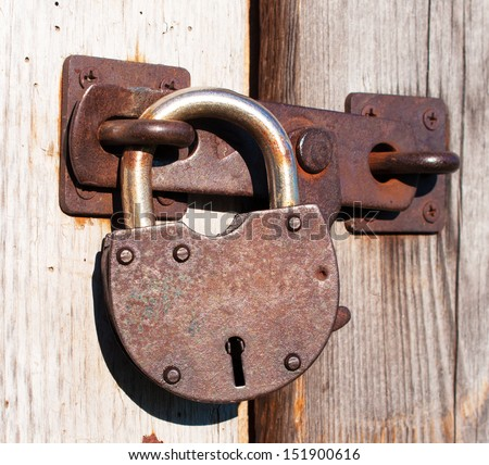 Old and rusty padlock on a wooden door. - stock photo