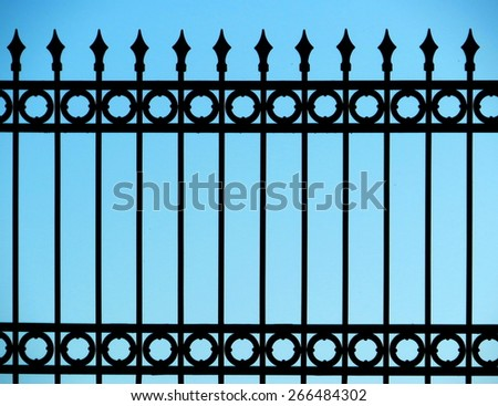 Old and rusty wrought iron fence on blue sky - stock photo