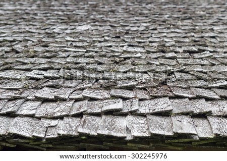 Old and weathered wooden roof shingle, blurred texture and background - stock photo
