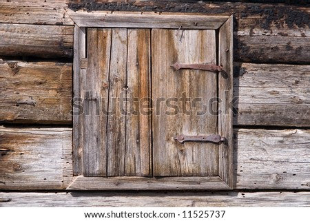 Old and weathered wooden window on a hut