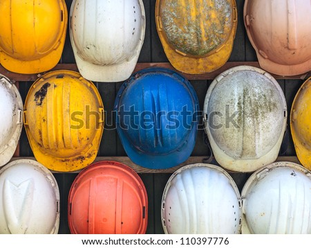 Old and worn colorful construction helmets - stock photo