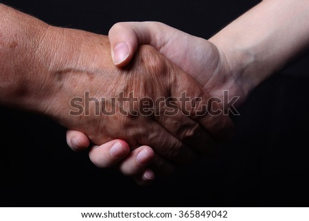 old and young hands are shaking hands on a black background