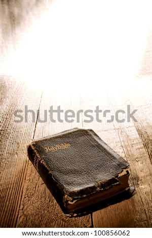 Old antique and damaged Holy Bible sacred Christian religious book in bright heavenly divine light on aged wood pulpit in a Protestant church - stock photo