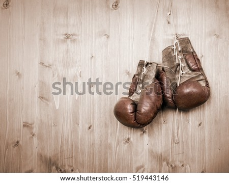 Old antique boxing gloves hanging against wooden wall / door. Landscape with copy space.