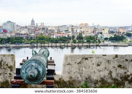 old antique cannon overlooking the blurring city of havana, Cuba - stock photo
