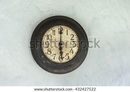Old antique clock hanging on the wall shows six o'clock. - stock photo