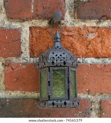 old antique ethnic lamp on the red brick wall - stock photo