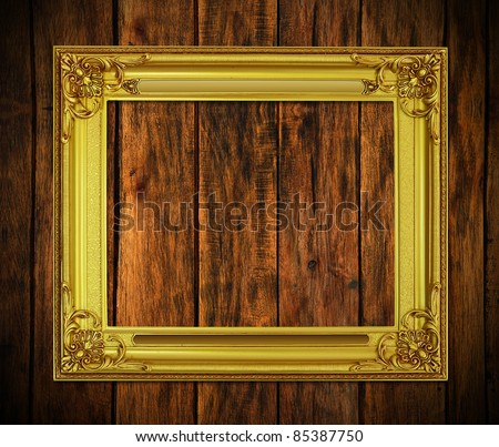 Old antique gold frame on wood texture background - stock photo