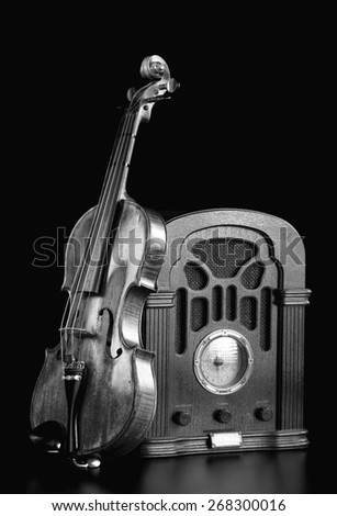 Old antique radio and violin in black and white. - stock photo