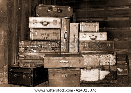 Old antique suitcases stacked up high in a station in sepia. - stock photo