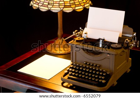 Old, antique, vintage, typewriter in writer's or author's area with lamp on black background - stock photo