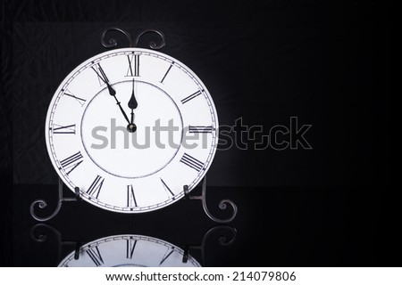 Old antique wall clock isolated on reflective floor, five minutes to twelve o'clock - stock photo