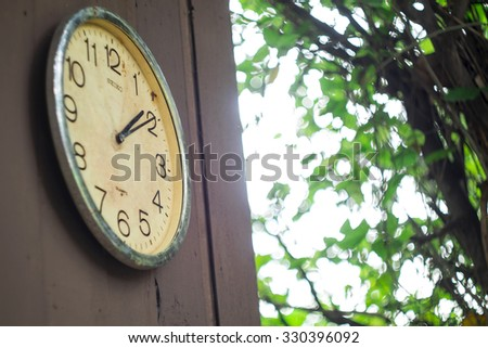 Old antique wall clock on wood outdoor - stock photo