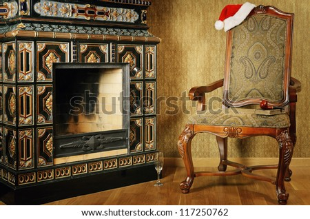 Old Antiques Armchair With Santa's Hat Near The Fireplace - stock photo