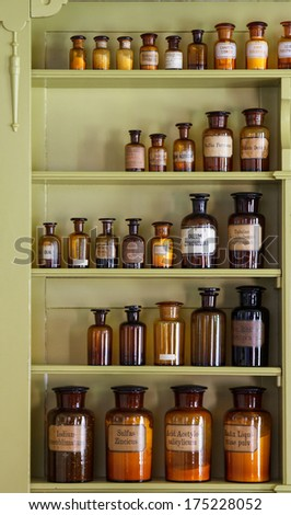 Old apothecary cabinet with storage jars with Latin labels - stock photo