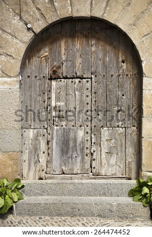 Old arched wooden door on Plaza Mayor, in Ainsa, Huesca, Spain in Pyrenees Mountains, an old walled town with hilltop views of Cinca and Ara Rivers - stock photo