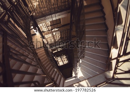 Old Architectural spiral marble stairs with black wrought iron railings in old building, palace - stock photo