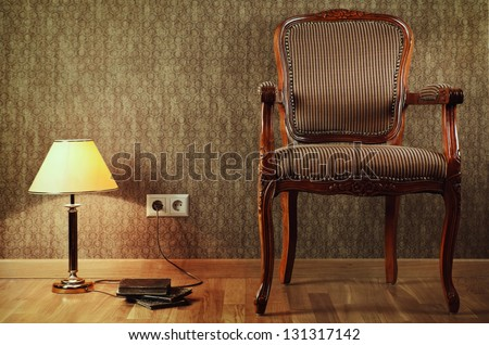 Old Armchair, Desk Lamp And Books On The Floor - stock photo