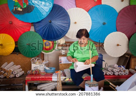 old  asian Woman in green shirt sitting, making a wooden umbrella in traditional umbrella factory,colorful umbrella background - stock photo