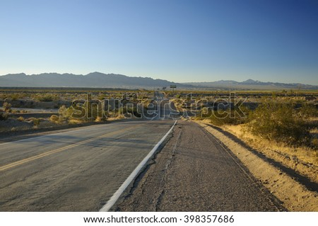 old asphalt road Route 66 through desert and blue sky  - stock photo