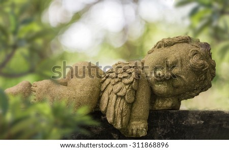 Old baby cupid in the garden, Sculpture at a Melbourne cemetery. - stock photo