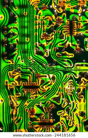Old backlighted PCB boar with electronics components - stock photo