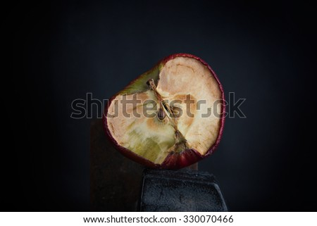 Old bad dry half apple on the black background - stock photo
