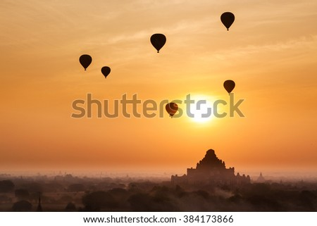 Old bagan in morning mist and silhouette of hot air balloon, tourists watching sunrise over ancient city, Myanmar (Soft focus) - stock photo