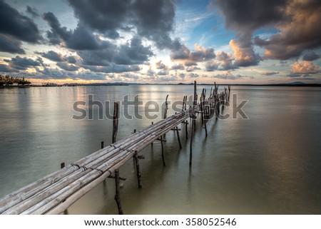 old bamboo wood pier and amazing twilight sky - stock photo