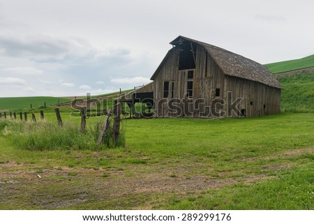 Old barn and barbed wire fence, Palouse, Washington - stock photo