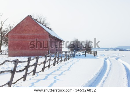 Old barn and fresh car tracks in snow - stock photo