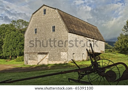 Old Barn and Plow - stock photo